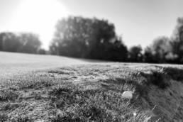 Een golfbal op de rand van een bunker in zwartwit
