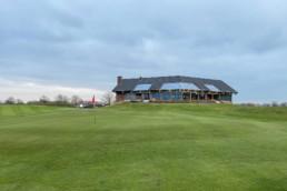 Green hole 18 en clubhuis van Golfbaan de Swinkelsche